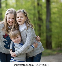 Cute three happy baby children friends of girls and boy people brother and sisters embracing outdoor in green forest on natural background