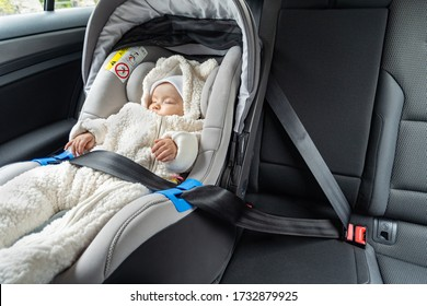 Das kleine, dreimonatige Baby schläft im Kindersitz auf dem Rücksitz des Wagens
