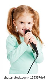 Cute three year old girl singimng with microphone.