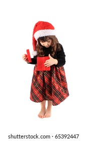 Cute three year old little girl dressed up in a fancy dress and christmas hat holding and looking into a a red giftbox standing barefoot on a white background