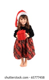 Cute three year old little girl dressed up in a fancy dress and christmas hat holding a red giftbox standing barefoot on a white background