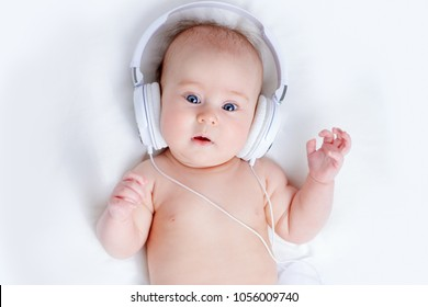Cute three-month-old baby listening to music in headphones.