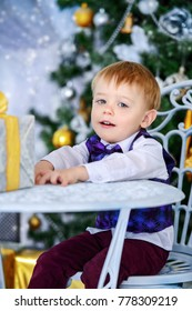 Cute three-year-old boy in elegant evening clothes sits in a beautiful room near a Christmas tree with gift box. Luxurious apartments decorated for Christmas. Merry Christmas and Happy New Year.