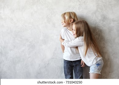 Cute timid preschool boy with blonde hair getting shy while beautiful little girl embracing him. Two happy adorable male and female kids hugging in studio, expressing their love, affection and care