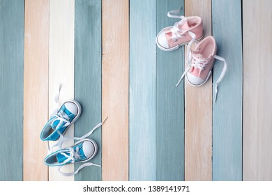 Cute tiny baby shoes on a wooden background with space for text