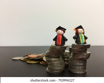Cute and tiny Japanese clay models of a boy and a girl in colorful graduation gowns standing on piles of money on dark floor and white background.