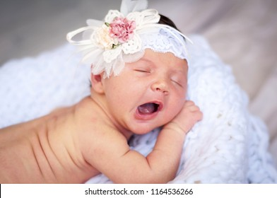 Cute tiny newborn Caucasian girl yawning closeup portrait. Kid bow elastic band on her head. A two week old infant baby girl stock image.