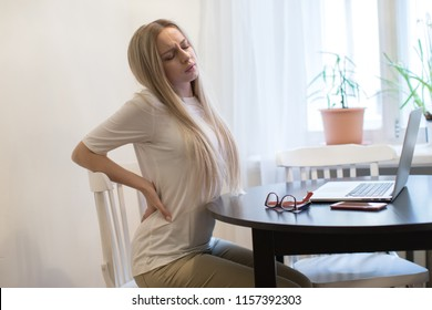 Cute tired young woman having pain, muscle or chronic nerve pain in her back after overwork on laptop, sitting on chair, indoors.Fatigue, overwork concept.Diseases of spine, scoliosis, osteoporosis