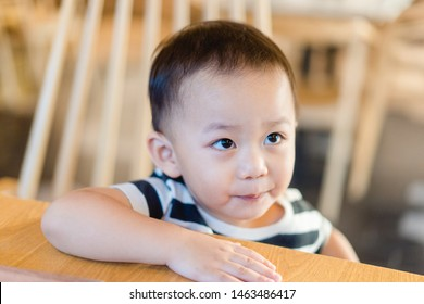 Cute toddler asian boy in a chair talking and asking father for hard question.Adorable baby learning to speak.Asian baby boy try to talk in table kitchen.