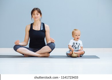 Cute toddler baby boy sitting in lotus pose with Tibetan singing bowl while his mother meditating in a yoga on grey background, Yoga together, motherhood, healthy lifestyle concept.