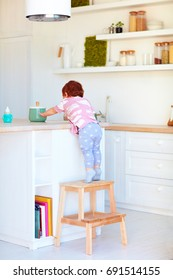 cute toddler baby climbs on step stool, trying to reach things on the high desk in the kitchen