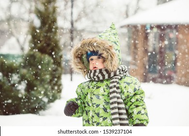 Cute toddler baby enjoy  first snow in  nature. Little boy emocions  and impressions in mazing beautiful winter snow fall.