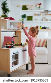 cute toddler baby girl playing on toy kitchen at home