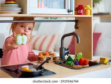 süßes kleines Mädchen, das zu Hause in der Spielzeugküche spielt, Eier braten und Sie mit einer Apfelscheibe behandeln, teilen wir es uns
