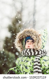 Cute toddler baby with knitted scharf enjoy and hapiness first snow in  nature. Little boy emocions  and impressions looking up to amazing snow fall.