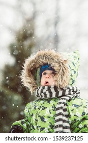 Cute toddler baby with knitted scharf enjoy first snow in  nature. Little boy emocions  and impressions looking up to amazing snow fall in winter.