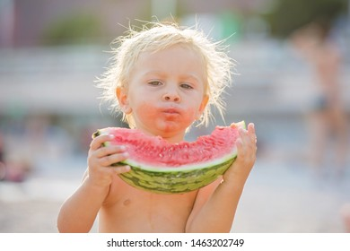 Cute toddler boy, blond child, eating watermelon on the beach coast on a sunny day