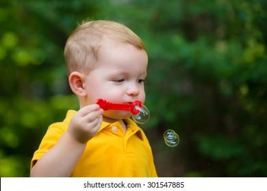 cute toddler boy blowing soap bubbles