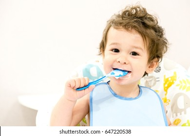 Cute toddler boy with blue spoon is yogurt. the child smiles. funny kid in a baby seat. beautiful 2 year old little boy eating