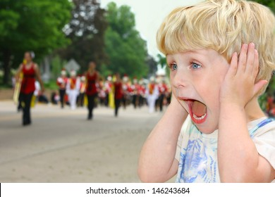A cute toddler boy covers his ears as he watches a school marching band walk by in a parade on a summer day