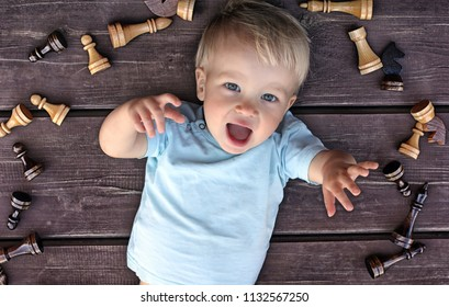 Cute toddler boy in frame of chess pieces on a rustic wooden background. Flatlay.