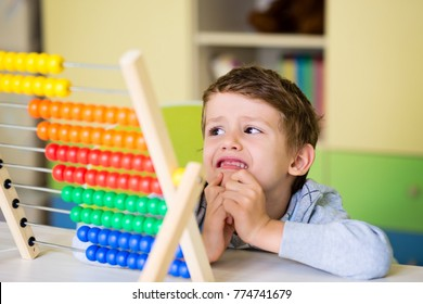 Cute toddler boy having difficulties using the abasus. Learning to count. Kids preschool activities and attention deficit.