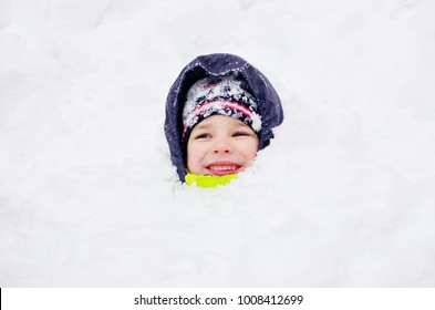A cute toddler boy having fun in a snowbank. Winter entertainment.