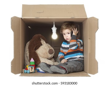 Cute Toddler Boy with his Stuffed Toy in Cardboard Box with Bare Light Bulb, representing cramped small place, Time to find some new Real Estate