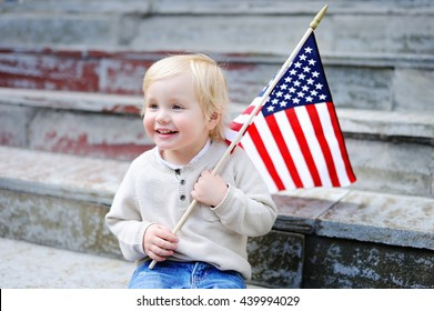 Cute toddler boy holding american flag. Independence Day concept.