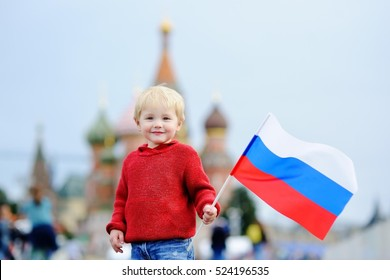 Cute toddler boy holding russian flag with Red Square and Vasilevsky descent on background