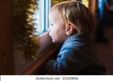 Cute toddler boy looking at the window at Christmas time