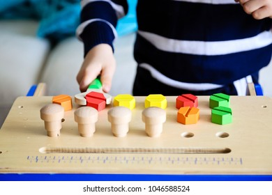 Cute toddler boy playing with construction blocks at home. Preschool activities for children. Early childhood development