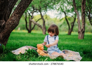 cute toddler boy playing and feeding his teddy bear with cookie in summer garden on colorful blanket