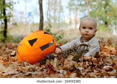 Cute toddler boy playing with pumpkin masque in the autumn park, outdoor