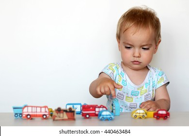 Cute toddler boy playing with wooden toy cars and point with finger on an accident on white background, safety and traffic regulations
