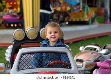 Cute toddler boy riding a truck on a merry-go-round