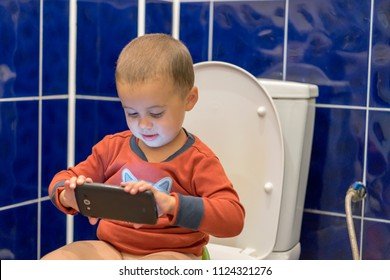 Cute toddler boy with smartphone in the bathroom. Little boy sitting on the toilet in the bathroom at home with using a smartphone. Toddler boy sitting on toilet with smartphone
