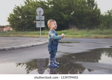Cute toddler boy standing in a puddle on the street smiling. Adorable smiling kid playing outdoors after rain, No retouch, matte filter.