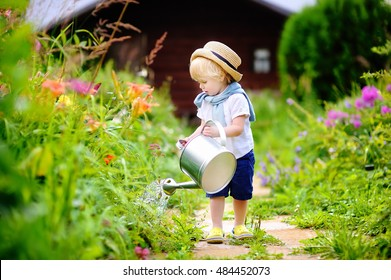 Cute toddler boy in straw hat watering plants in the garden at summer sunny  day 906c9a56631b