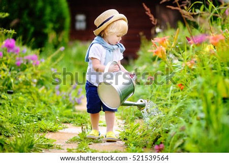 Cute toddler boy in straw hat watering plants in the garden at summer sunny  day 4f8b7fd827c1