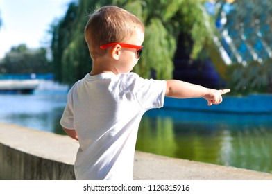 Cute toddler boy walks in a park in sunglasses and a white T shirt showing a finger in the distance
