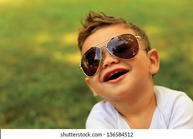 Cute toddler boy wearing sunglasses and looking at the camera