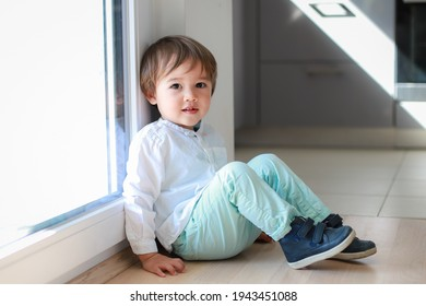 Cute toddler boy wearing white shirt and green pants sitting on the floor with smiling face. Happy mixed race Asian-German infant relaxing at home. Adorable fashion kid.