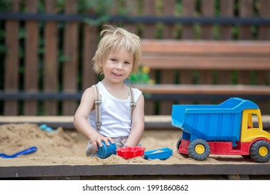 Cute toddler child, blond boy, playing in the sandpit in the park, summertime