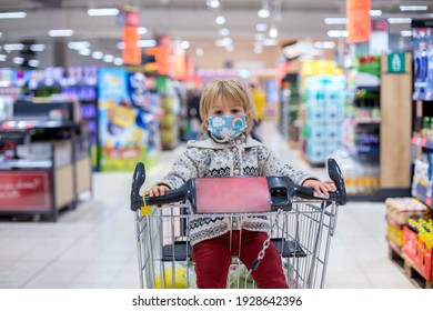 Cute toddler child, boy, wearing medical mask in supermarket store during covid pandemic lockdown