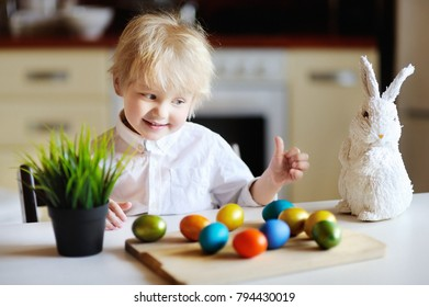 Cute toddler child playing with easter eggs on Easter day. Little boy celebrate Easter at home.