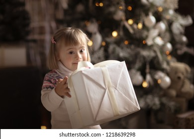 Cute Toddler with Down Syndrome in a sweater and jeans with christmas gifts, in a real interior near the Christmas tree. Concept New Year and Christmas,