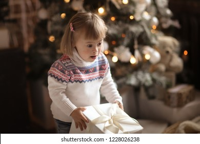 cute toddler with down syndrome in a sweater and jeans with christmas gifts in a