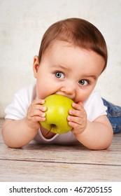 Cute toddler eating apple