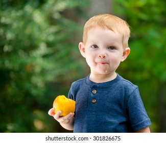 cute toddler eating fresh summer peach